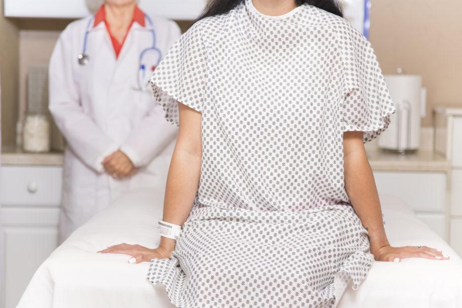 mulher sentada na mesa da ginecologista
