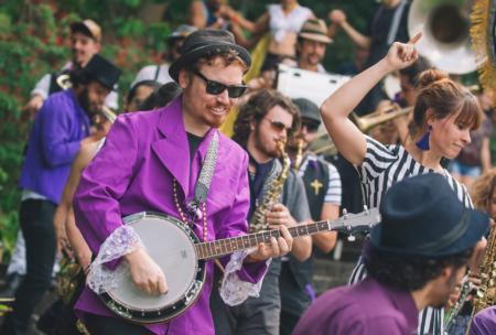 homem com terno roxo tocando bandolim ao ar livre no festival fam no parque burle marx em 2018