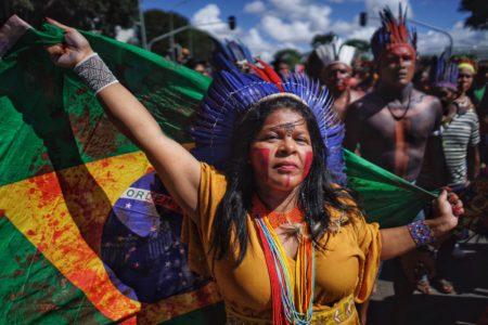 a indígena Sonias Guajajara segura a bandeira do brasil cheia de sangue