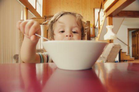 criança na mesa comendo com colher