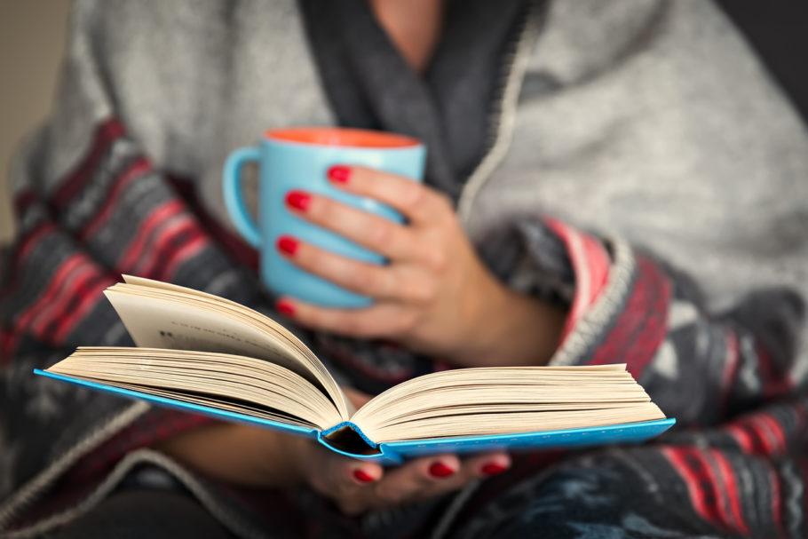 mulher com caneca e livro na mão