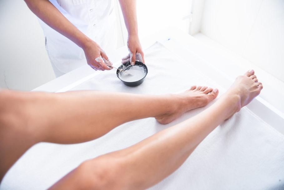 osmetologista preparando argila branca para procedimento enquanto senhora deitada em uma maca node spa