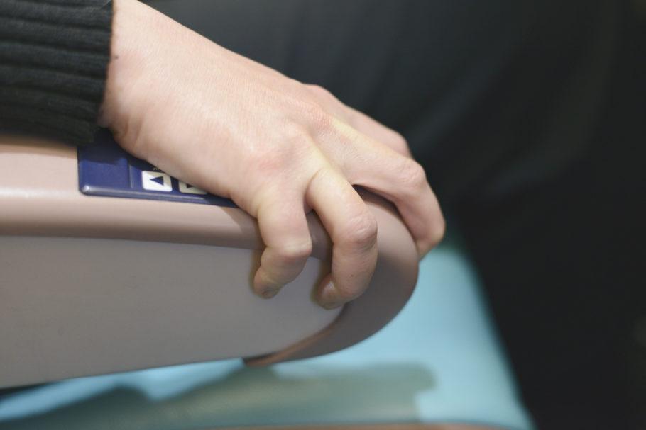 mulher segurando o braço do assento do avião