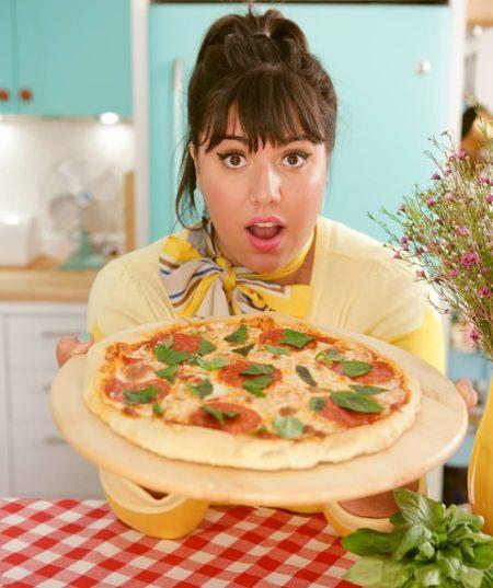 apresentadora Raiza Costa segurando uma pizza com cara de espanto