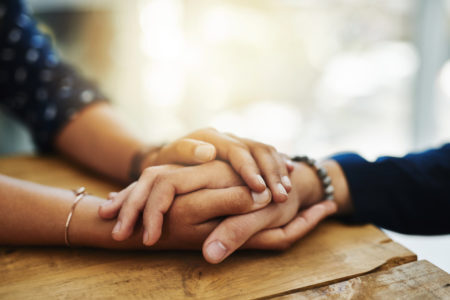 duas pessoas com as mãos entrelaçadas em sinal de apoio e ajuda