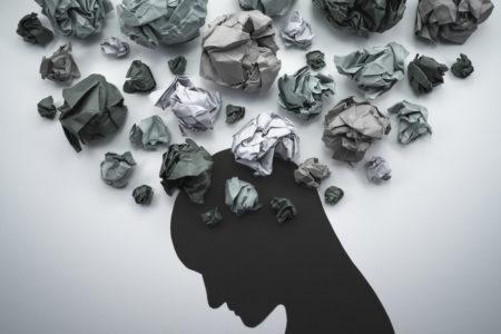 Imagem conceitual representando a ansiedade e sentimentos negativos onde uma silhueta humana pensa bolas de papel amassado