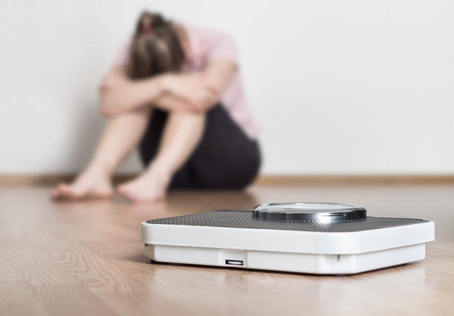mulher chorando atrás da balança
