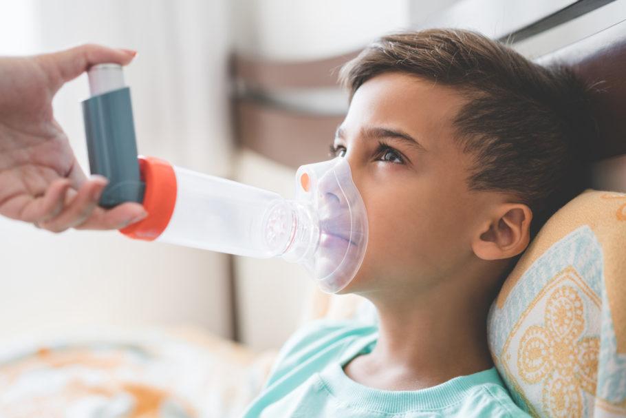 menino usando aparelho para asma