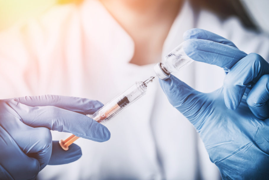 mulher segurando injeção com vidro de vacina
