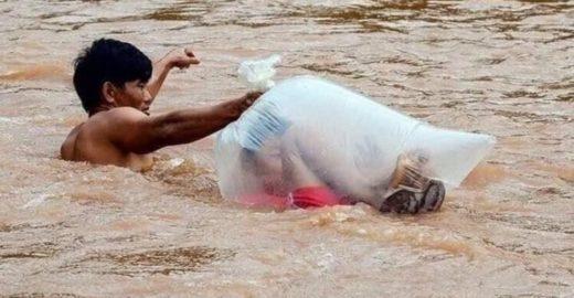 Crianças cruzam rio em saco plástico para chegar a escola no Vietnã