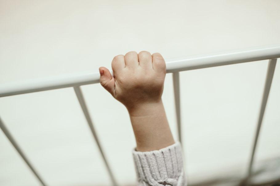 Criança se apoia em berço