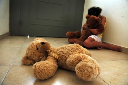 criança vítima de abuso infantil sentada e chorando no canto abraçado a um urso de pelucia, enquanto outro urso de pelucia está jogado no chao em frente a ela