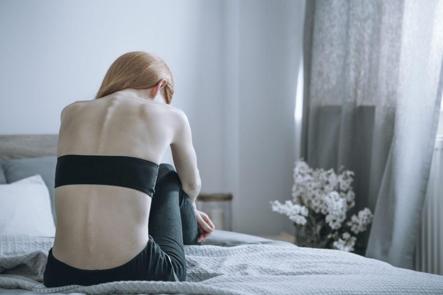 mulher com anorexia sentada na cama