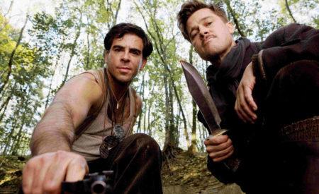 cena com brad pitt e Eli Rot de bastardos inglórios olhando para a camera com uma arma e uma faca na mão