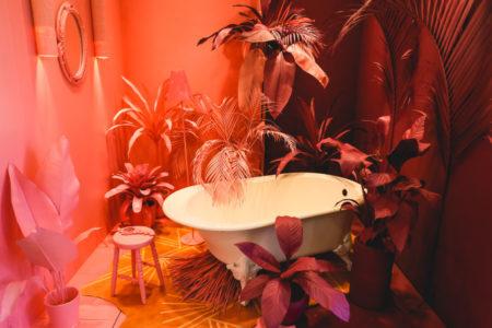 uma banheira em uma sala com iluminação rosa