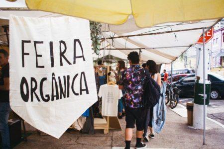 """pessoas entre as barracas da feira jardim secreto; à frente da foto há uma bandeirola branca com """"feira orgânica"""" escrito"""