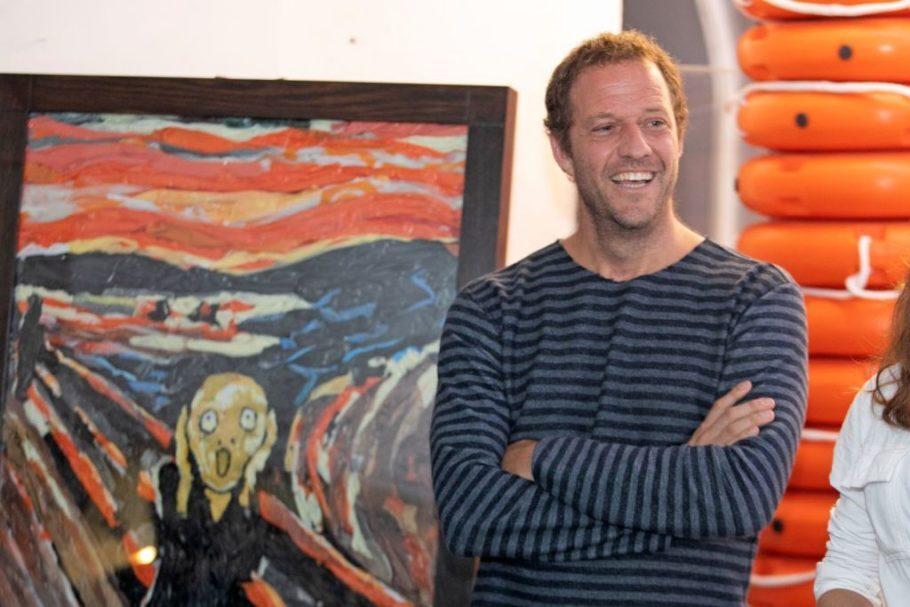 """artista com o quadro """"O grito"""", de Munch,, ao fundo"""
