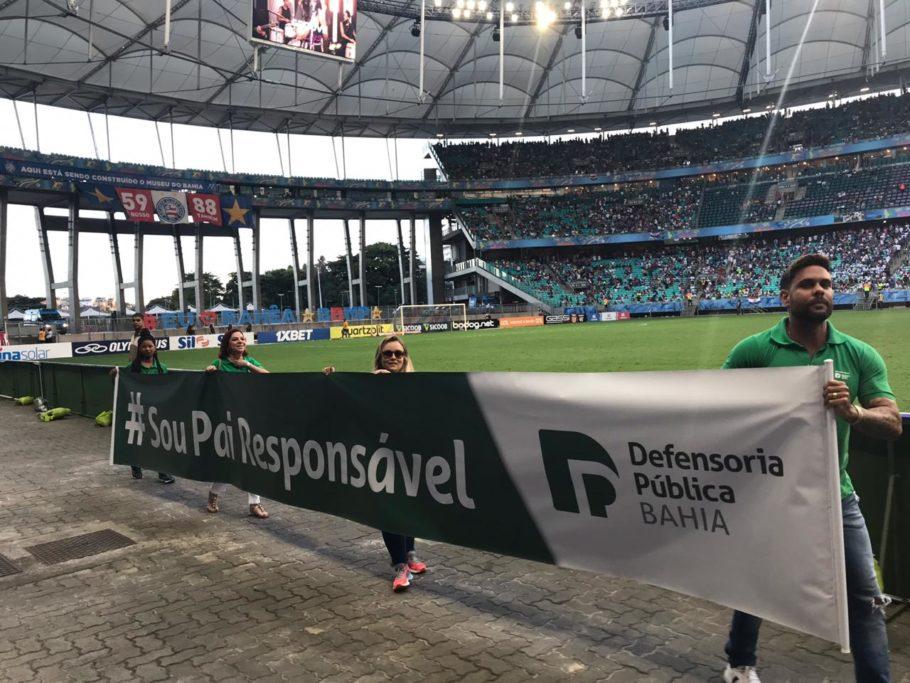 Defensores públicos carregam faixa da campanha em favor do reconhecimento da paternidade em dia de jogo do Bahia