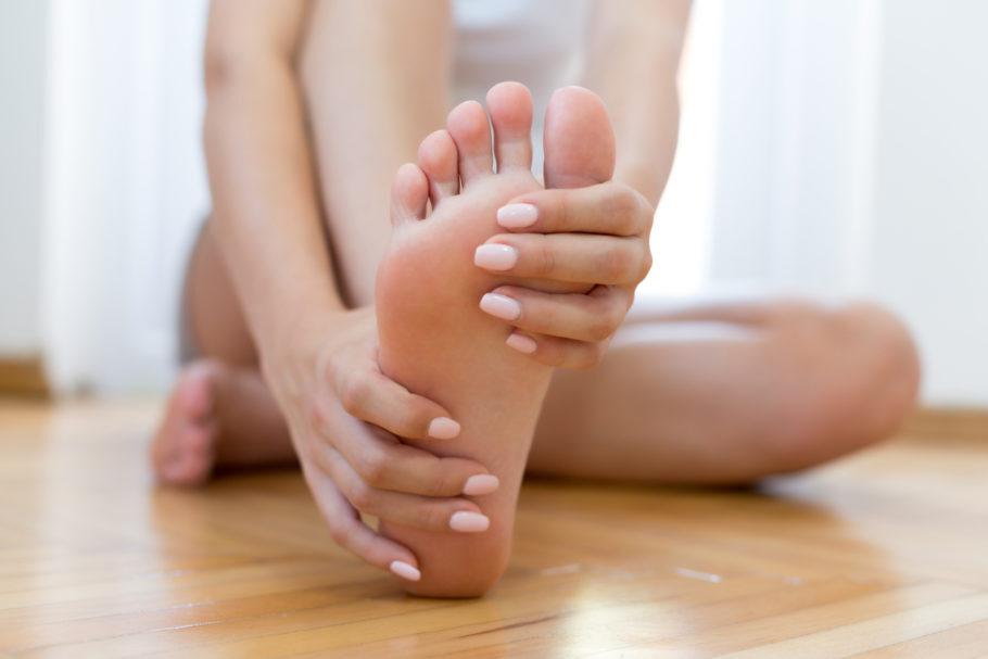 mulher sentada no chão tocando o próprio pé