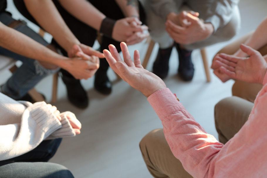 pessoas sentadas em roda fazendo terapia em grupo