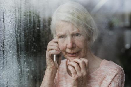 mulher idosa ao telefone reportando crime de violência contra idosos