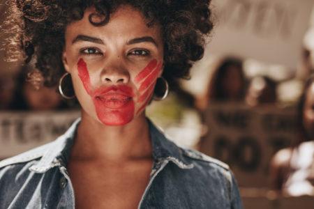 mulher negra com uma marca de mão espalmada pintada com tinta vermelha em sua boca demonstrando violência doméstica em uma mulher