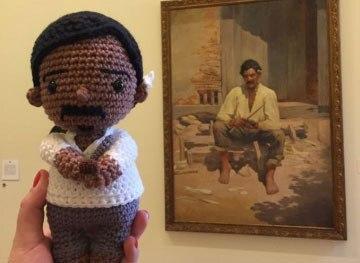 boneco de crochê ao lado da pintura