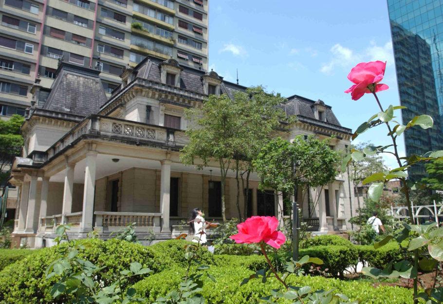 fachada da casa das rosas com rosas rosa em primeiro plano