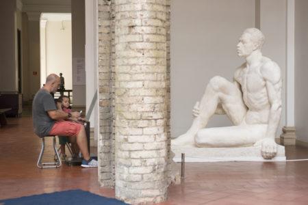 pai e filho observam escultura na pinacoteca