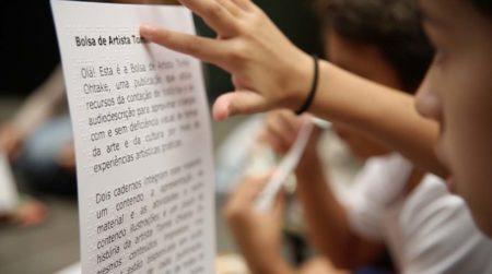 criança lendo em braille texto sobre a atividade bolsa de artista do tomie ohtake