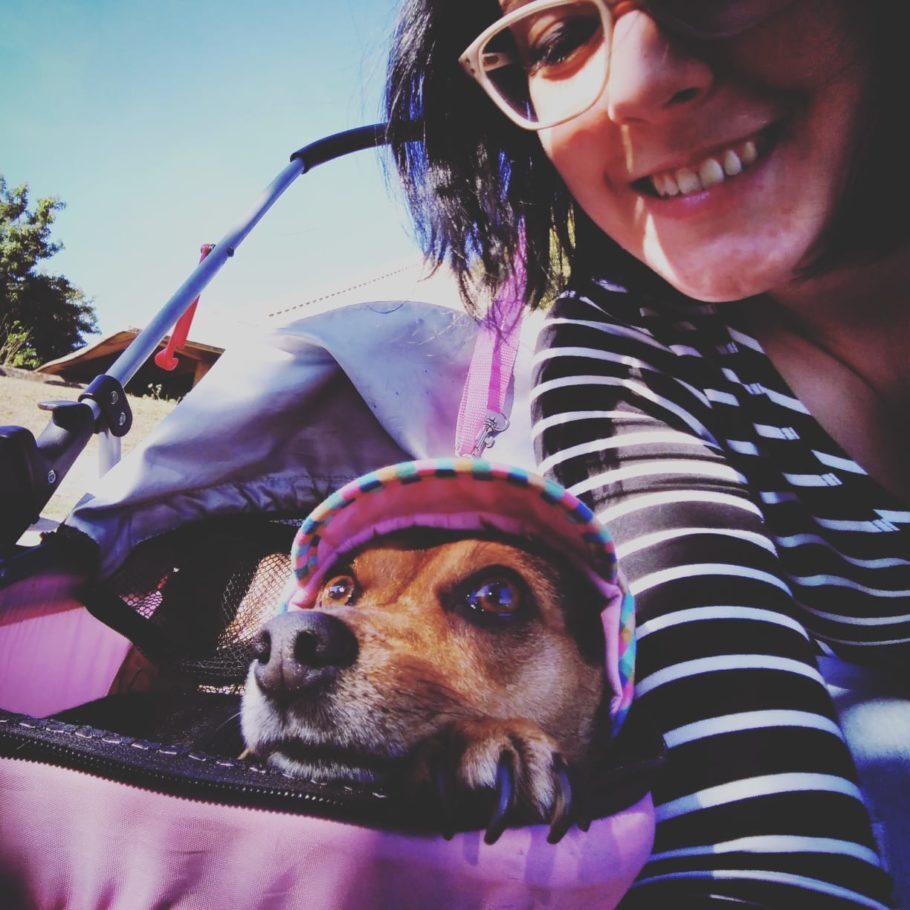 Marina com a cachorrinha Muriel em um carrinho para cachorro