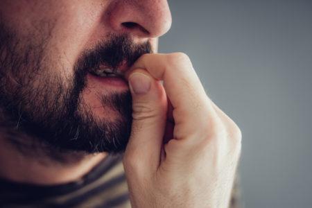 homem com ansiedade roendo unhas