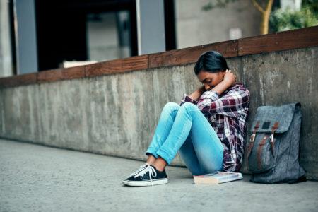 mulher sentada na rua chorando em crise de ansiedade
