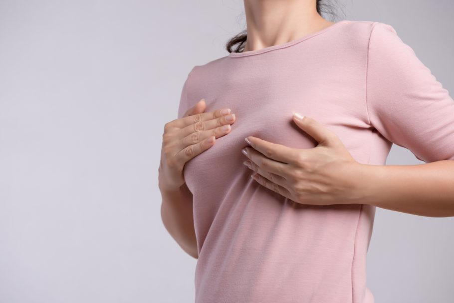 mulher com blusa rosa apalpando o seio