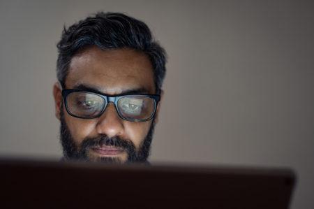 homem de óculos usando um notebook