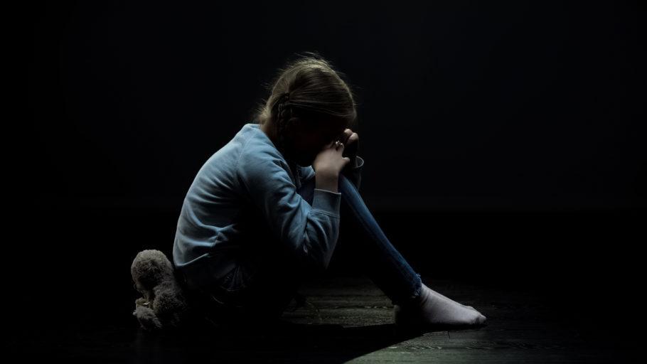 criança no quarto escuro