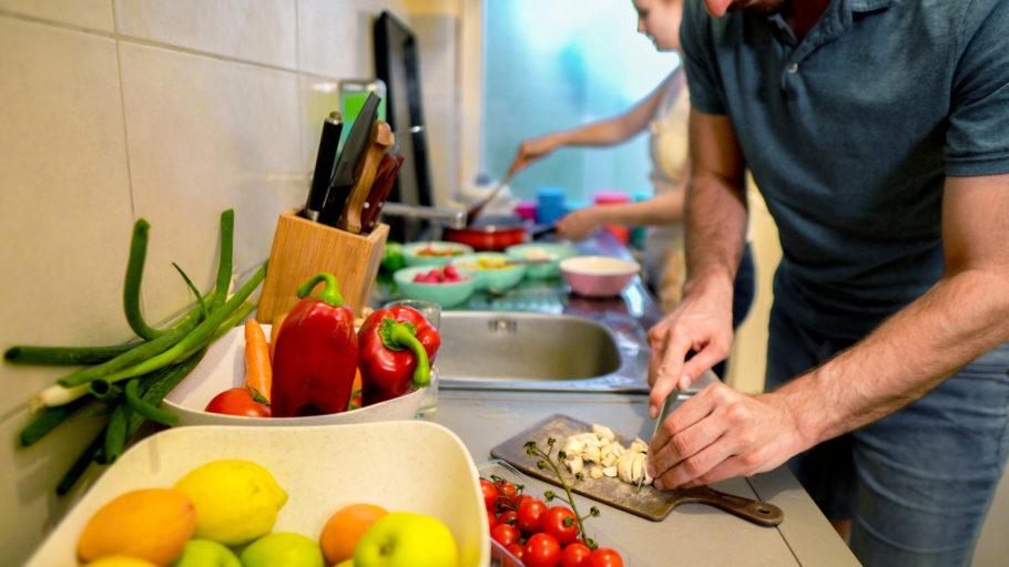 casal preparando comida com vários vegetais