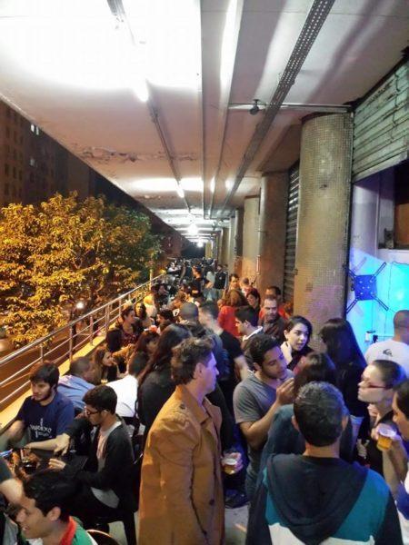 pessoas em happy hour na varanda do edifício maletta