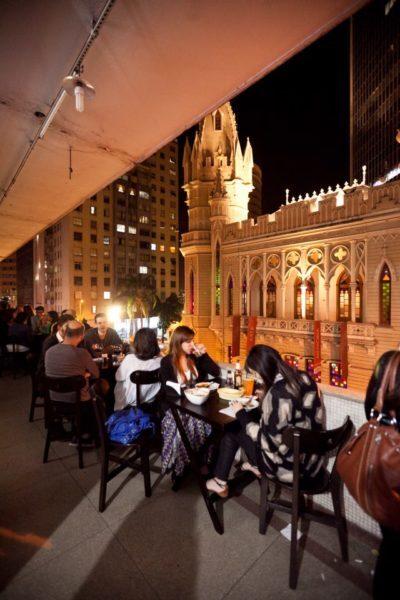 pessoas bebendo na varanda do edifício maletta