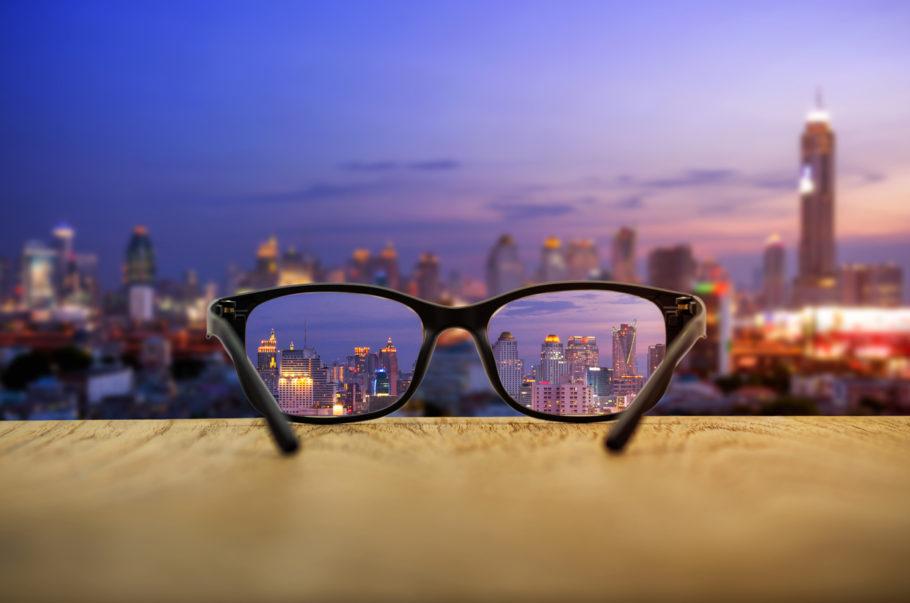 óculos em uma mureta focando prédios ao fundo