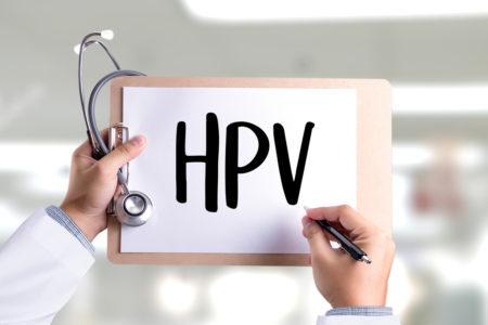 mãos de um médico segurando uma prancheta com uma folha onde está escrito HPV