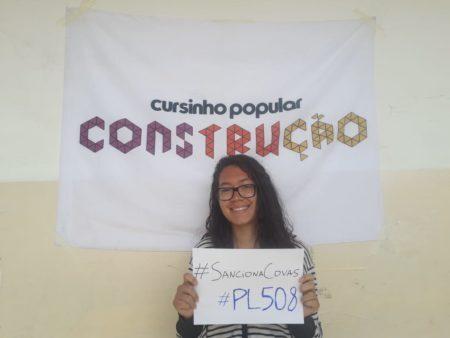 aluna segura placa de campanha