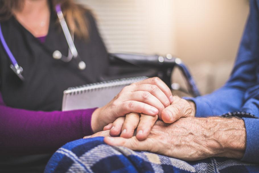 médica segurando a mão de paciente idoso