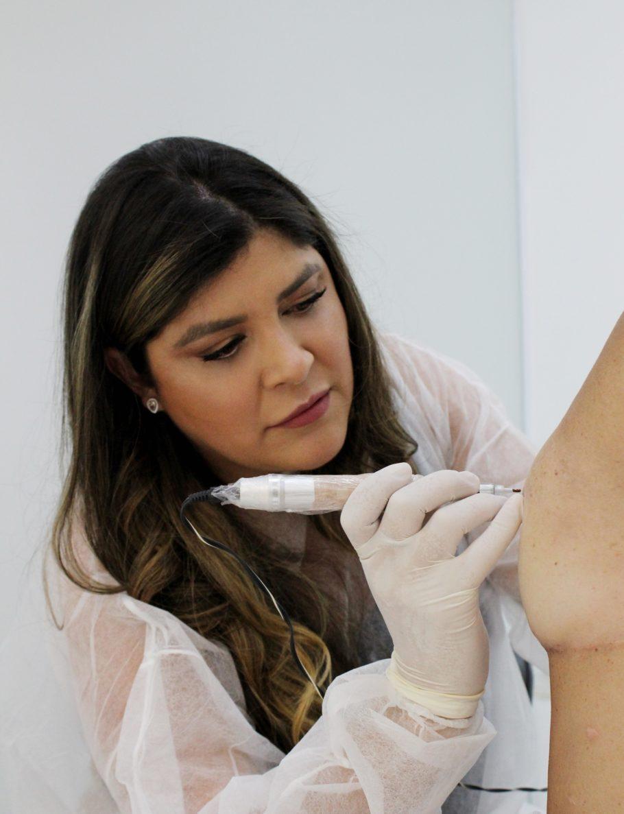 mulher fazendo micropigmentação no seio de outra