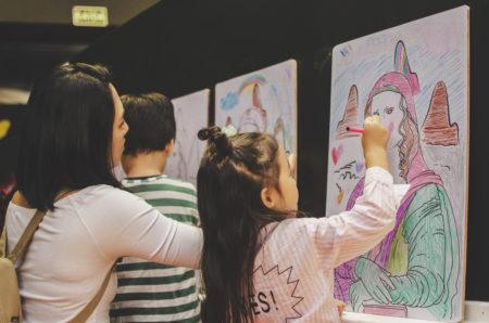 crianças pintando releitura da monalisa na exposição de da vinci no museu da imaginação