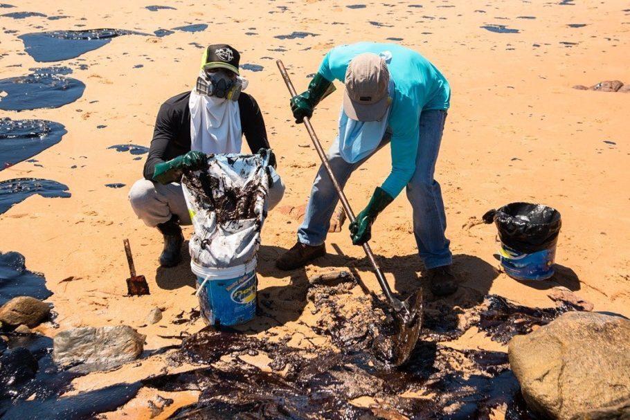 voluntários retiram óleo de praia