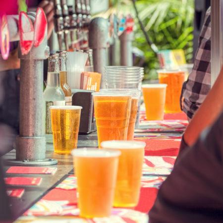 copos de plástico com cerveja dispostos na mesa de um festival