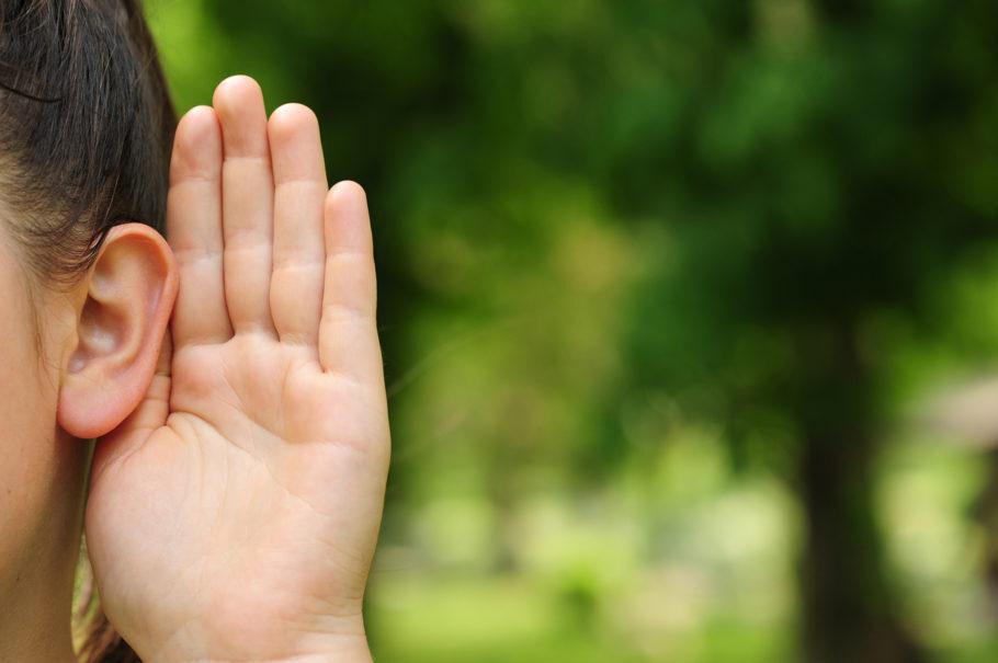 menina com a mão no ouvido tentando ouvir