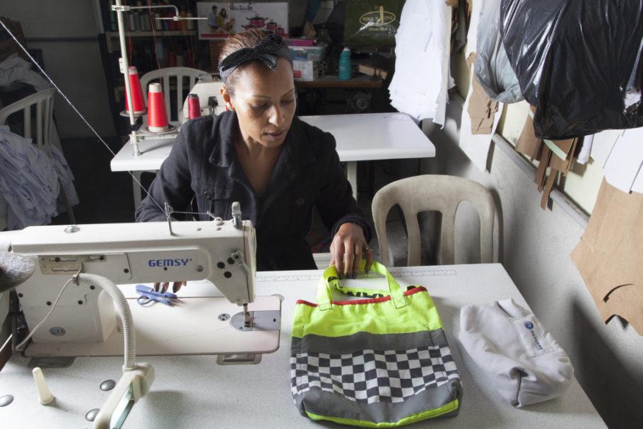 mulher de ONG costura produto com resíduo têxtil