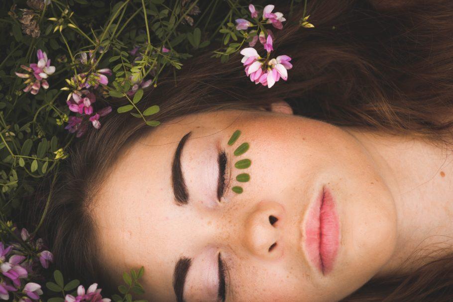 mulher deitada na grama com olhos fechado e folhas em seu rosto